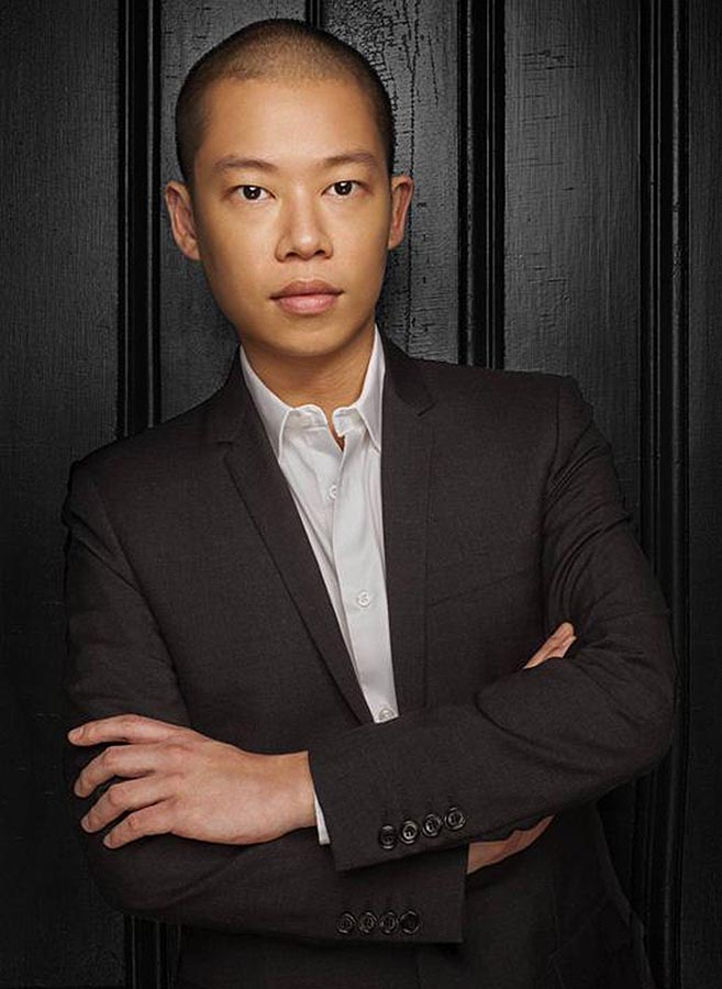 Jason Wu in suit with arms folded